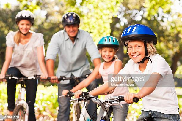 Happy family smiling while cycling at park