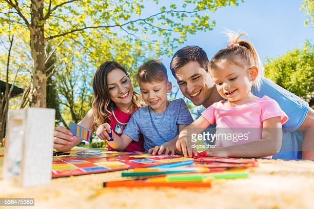 Happy family spending a day outdoors and playing board game.