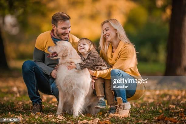 Glückliche Familie einen Tag mit ihrem golden Retriever in der Natur zu verbringen.