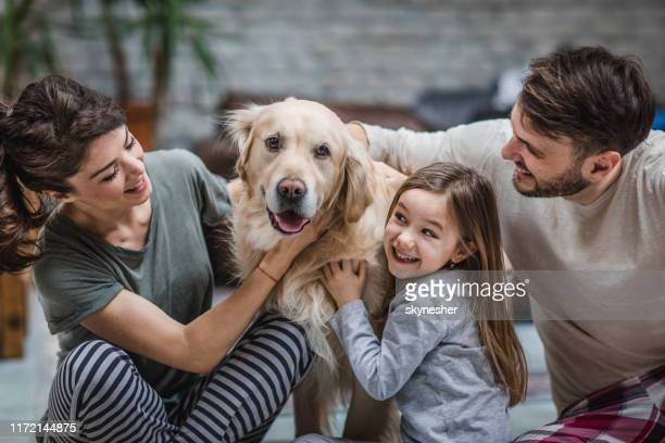 famiglia felice che trascorre del tempo con il proprio cane a casa. - animale domestico foto e immagini stock