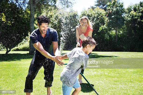 Happy family splashing water with garden hose