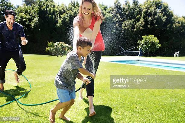 Happy family splashing water with garden hose