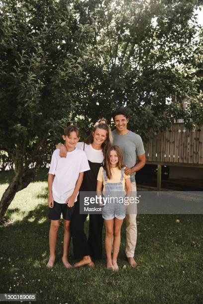 happy family standing against tree in back yard - four people bildbanksfoton och bilder