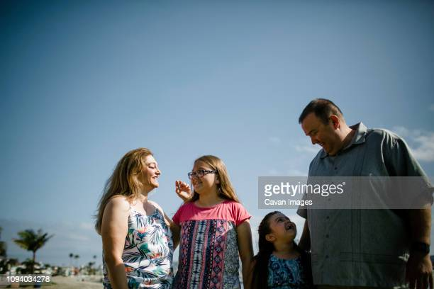 happy family standing at beach against sky during sunny day - fat guy on beach stock pictures, royalty-free photos & images