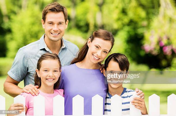 Happy Family Standing Behind PIcket Fence In Garden