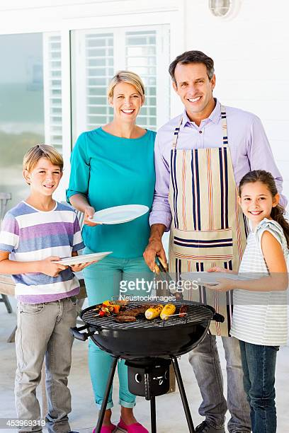 Happy Family Standing By Barbecue On Patio