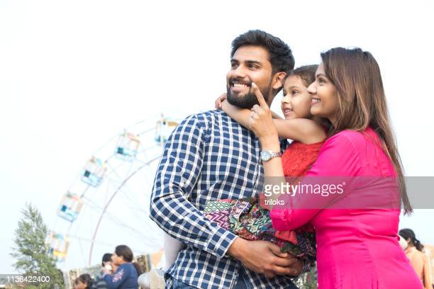 happy family standing in front of ferris wheel - indian subcontinent ethnicity stock pictures, royalty-free photos & images