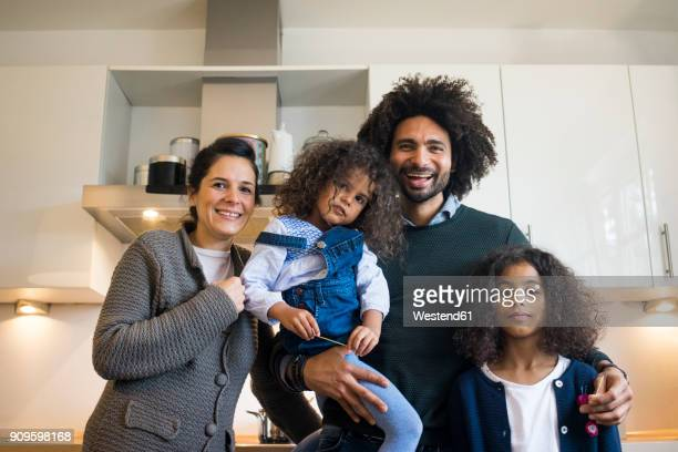 happy family standing in kitchen, laughing - mixed race person stock pictures, royalty-free photos & images