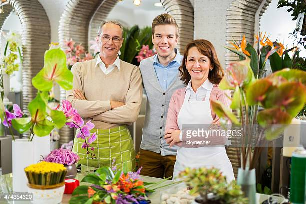 Happy family standing in their family flower shop.