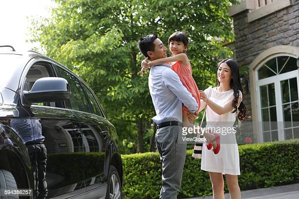 Happy family standing next to the car