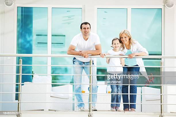 Famille heureuse, debout sur le balcon.