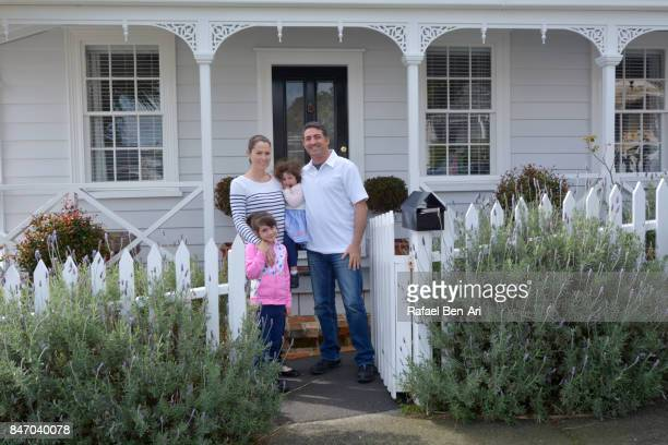 happy family stands outside their new home - rafael ben ari photos et images de collection