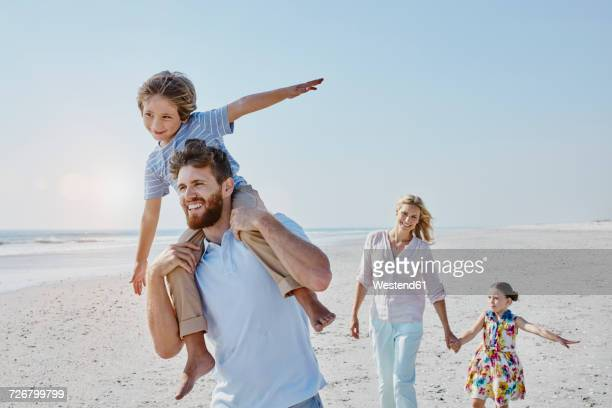 Happy family strolling on the beach