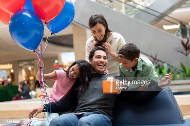 happy family surprising father with a gift at a shopping center - fathers day stock pictures, royalty-free photos & images
