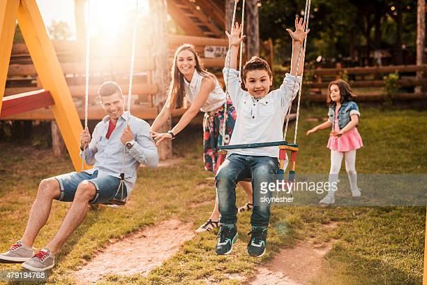 Happy family swinging on playground at sunset.