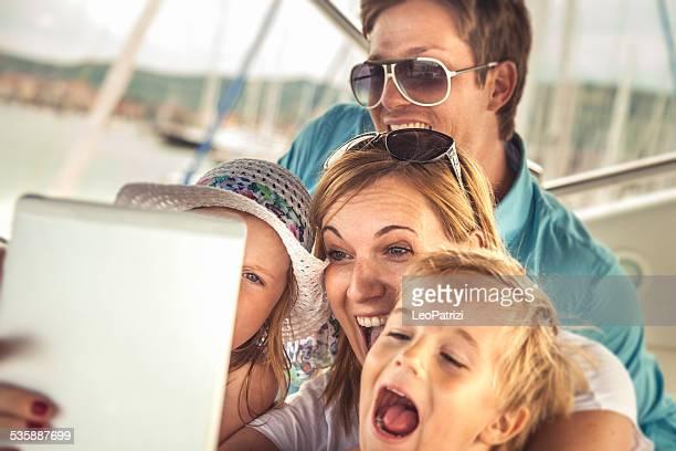 Happy family tome un autorretrato en tableta con hijos