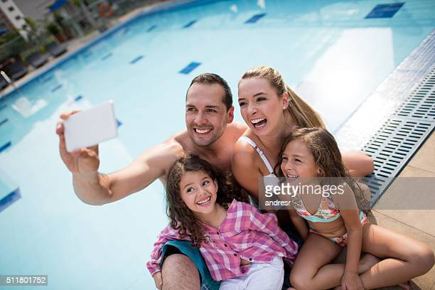 Happy family taking a selfie by the pool
