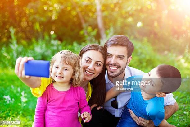 Famille heureuse en prenant un selfie dans le parc