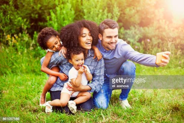 gelukkige familie een selfie te nemen in het park - gemengde afkomst stockfoto's en -beelden