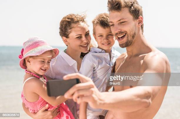 Happy family taking a selfie on the beach.