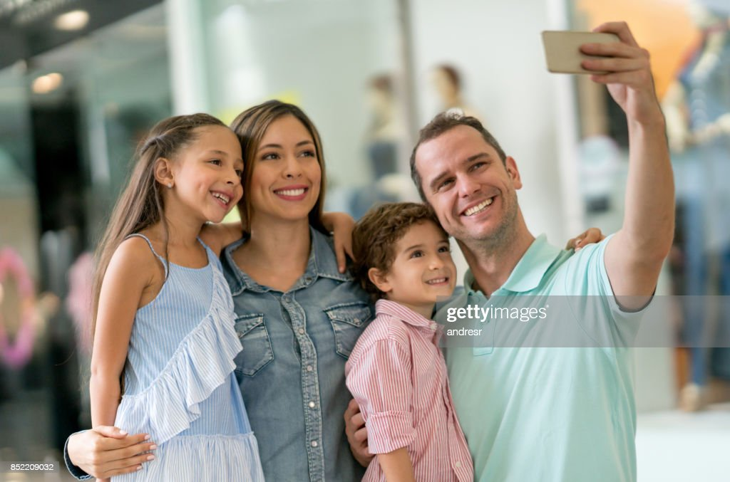 Happy family taking a selfie while shopping at the mall : Stock Photo
