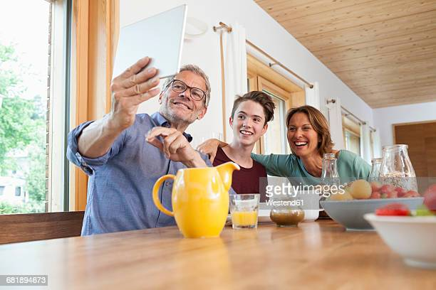 Happy family taking a selfie with tablet at dining table