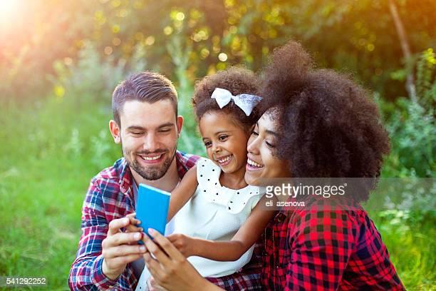 Heureuse famille prenant un selfie par téléphone intelligent en plein air