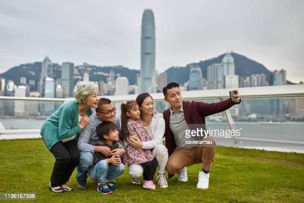 Happy family taking selfie in central park at dusk