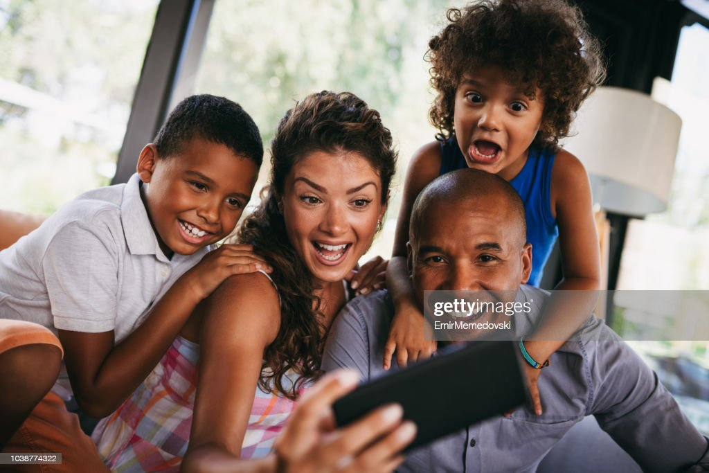 Happy family taking Selfie while sitting in cafe : Stock Photo