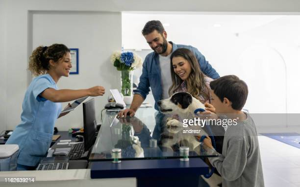 happy family taking their dog to the vet - animal hospital stock pictures, royalty-free photos & images
