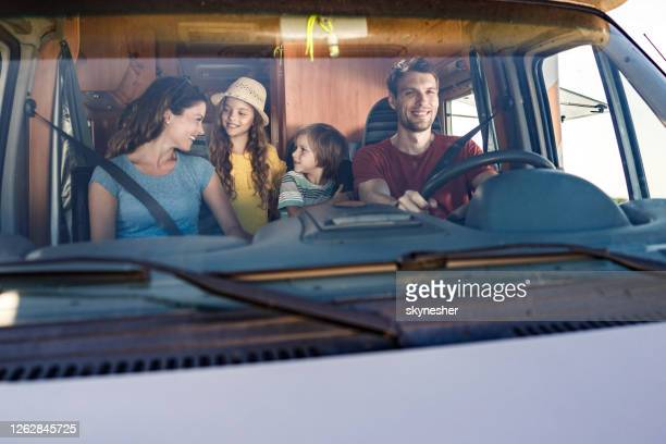happy family talking while driving inside of a camp trailer. - camper trailer stock pictures, royalty-free photos & images
