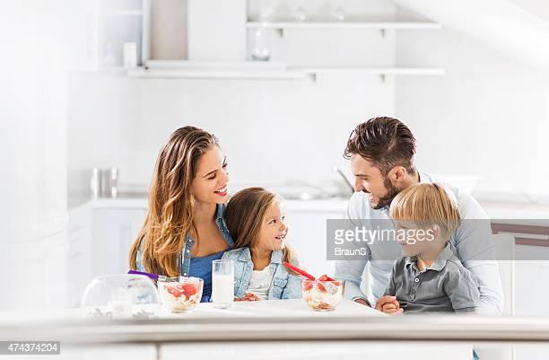 Familia feliz hablando mientras almuerza juntos.