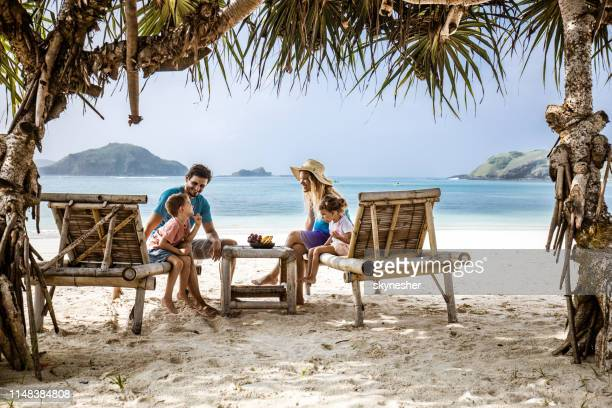 happy family talking while relaxing on deck chairs at the beach. - family beach holiday stock pictures, royalty-free photos & images