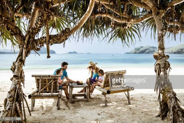 feliz familia hablando mientras se relaja en tumbonas en la playa. - lombok fotografías e imágenes de stock