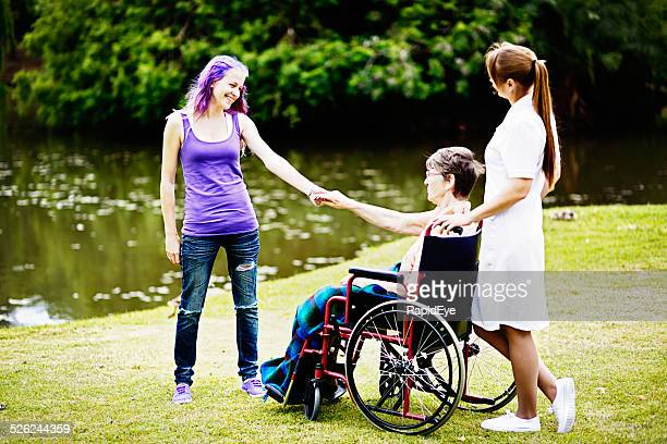 Happy family! Teenage non-conformist holds hands with grandmother; nurse watching