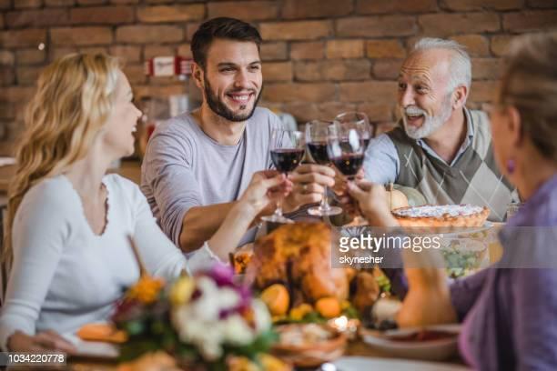 heureuse famille grillage avec du vin tout en ayant un dîner de thanksgiving fête dans la salle à manger. - bonne fete papa photos et images de collection