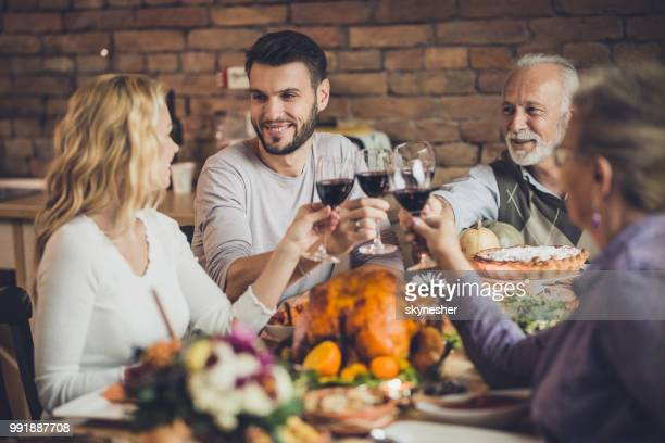Happy family toasting with wine while having a Thanksgiving dinner party in dining room.