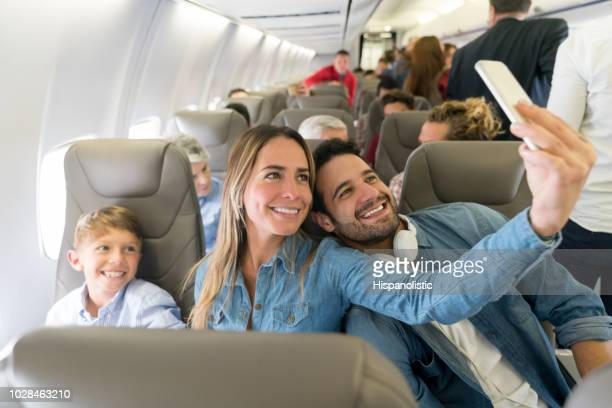 happy family traveling by plane and taking a selfie - aeroplane stock pictures, royalty-free photos & images