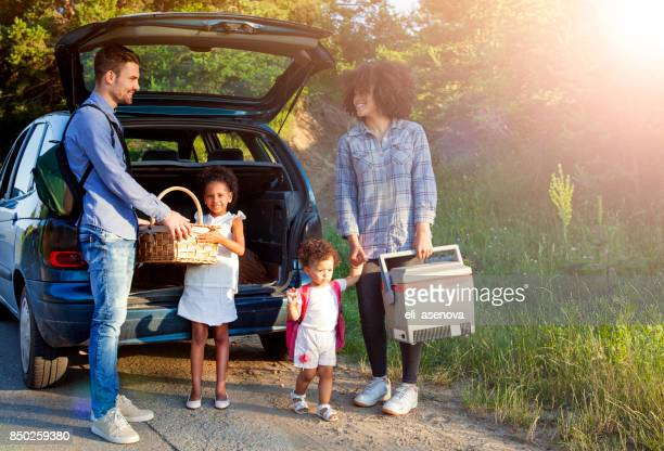 Happy family unloading luggage from the car for summer vacation.