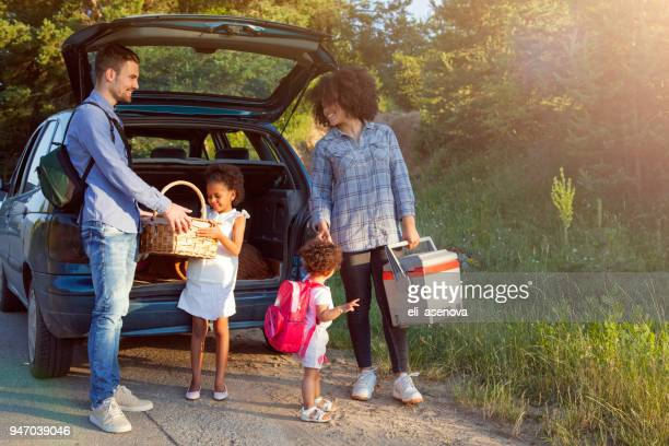 happy family unloading luggage from the car for summer vacation. - road trip stock pictures, royalty-free photos & images