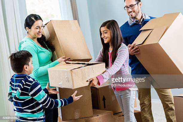 Happy family unpacks in their new home