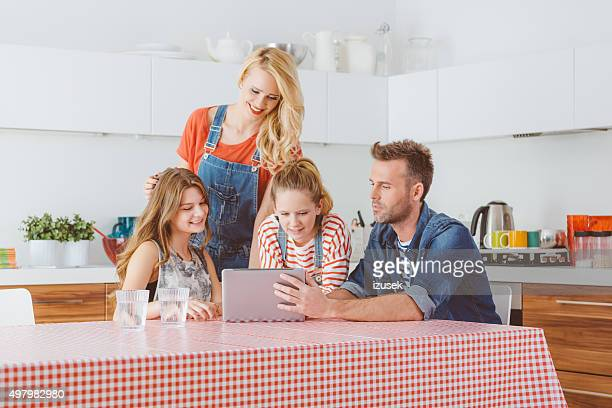 happy family using a digital tablet in the kitchen - izusek stock pictures, royalty-free photos & images