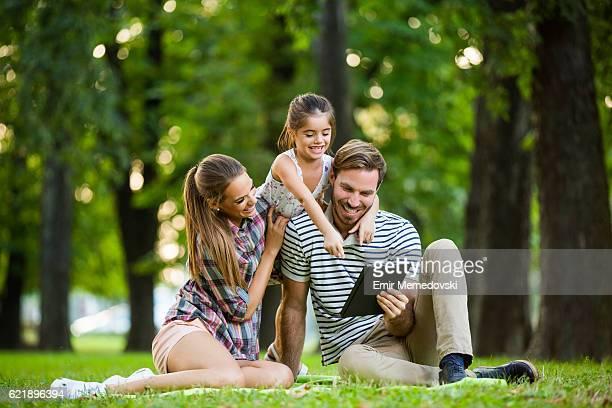 Glückliche Familie mit Digitaltablett im park.