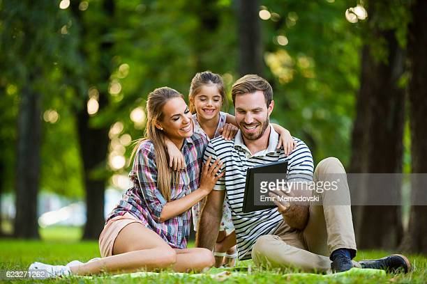 Happy family  using digital tablet in the park.