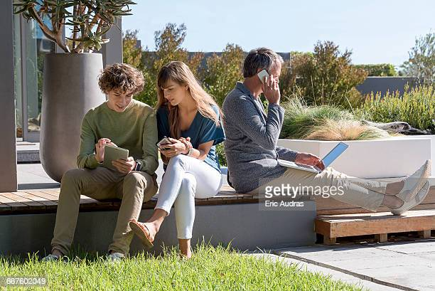 Happy family using electronic gadgets in a garden