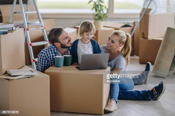 Glückliche Familie mit Laptop beim Umzug in neues Zuhause.