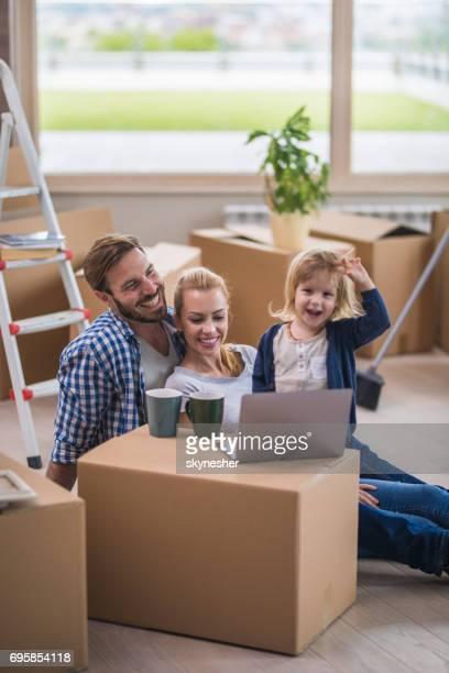 Glückliche Familie mit Laptop und entspannen Sie vom Auspacken ihre Habseligkeiten in neue Wohnung.
