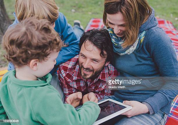 Happy family using tablet pc outdoor.