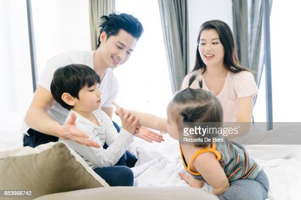 Happy family waking up in the morning, playing in bed