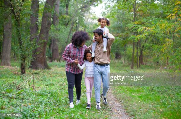 happy family walking along a path in the woods - mixed race person stock pictures, royalty-free photos & images